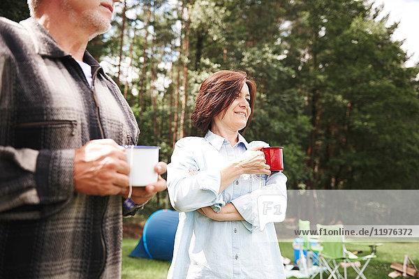 Ein reifes Paar steht neben dem Zelt und hält eine Tasse Tee