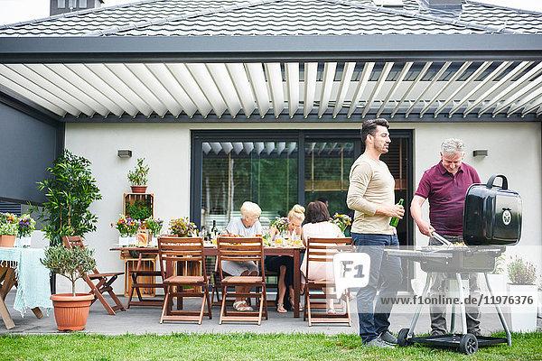 Zwei Männer grillen beim Familienessen auf der Terrasse