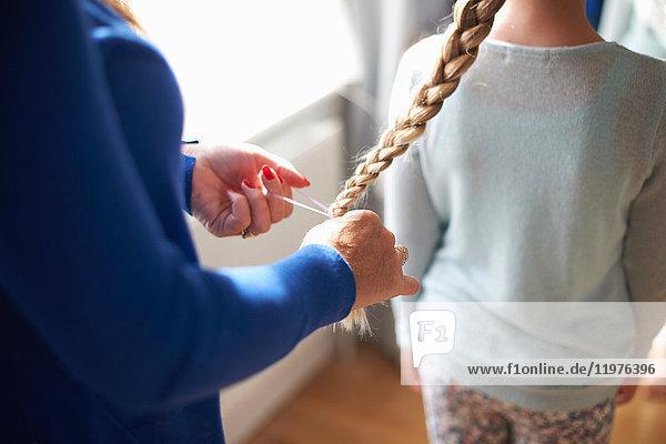 Schrägansicht einer Mutter  die einer Schulmädchen-Tochter die Haare flechtet