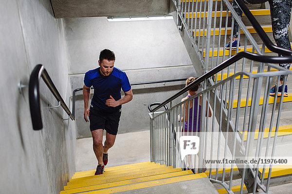 Junger männlicher Läufer läuft eine Hallentreppe hinauf