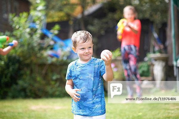 Spitzbübischer Junge hält Wasserballon im Garten