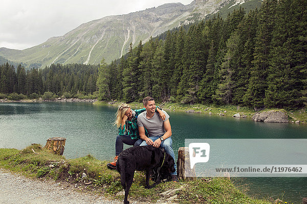 Couple with dog  hiking  sitting by lake  Tirol  Steiermark  Austria  Europe