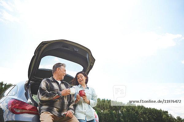 Älteres Paar steht neben dem Auto  hält Blechbecher  lächelt  niedriger Blickwinkel