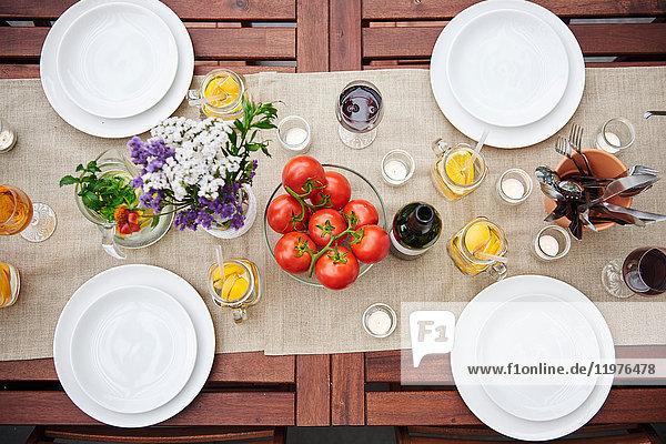 Draufsicht auf einen Tisch mit Blumen und Strauchtomaten zum Mittagessen auf der Terrasse