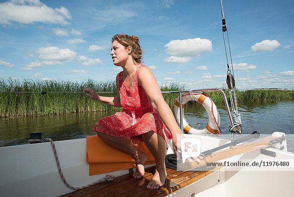 Woman on boat in the Frisian lake district in vintage dress  Sneek  Friesland  Netherlands