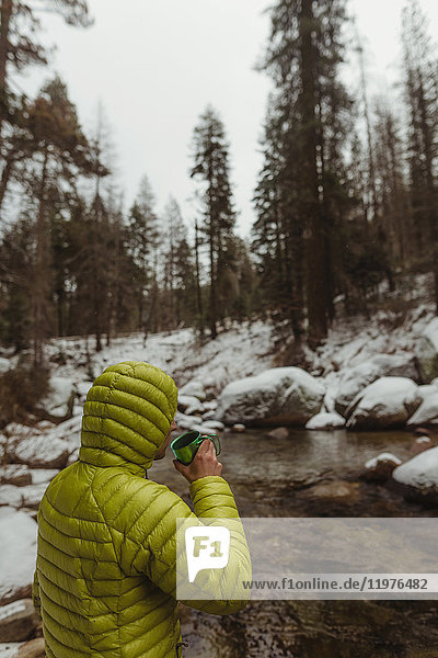 Young male hiker drinking coffee by snowy forest river  Sequoia National Park  California  USA