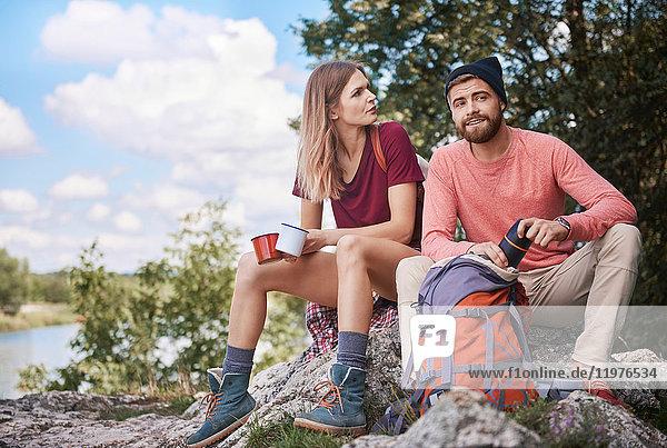 Paar beim Wandern  auf Felsen sitzend und Emaillebecher haltend  Krakau  Malopolskie  Polen  Europa
