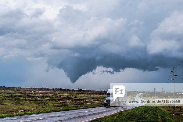 Lastwagen auf nasser Straße  Tornado hebt sich südlich von Waynoka im Hintergrund  Oklahoma  USA