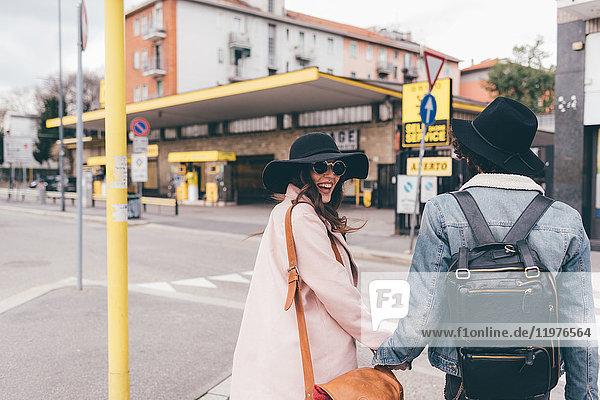 Junges Paar im Freien  Straße überqueren  Händchen haltend  lachend  Rückansicht