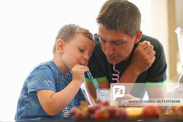 Junge und Vater teilen sich frischen Smoothie in der Küche