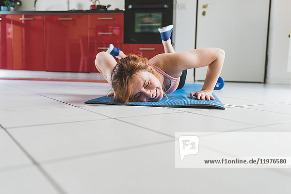 Young woman doing push ups on kitchen floor laughing
