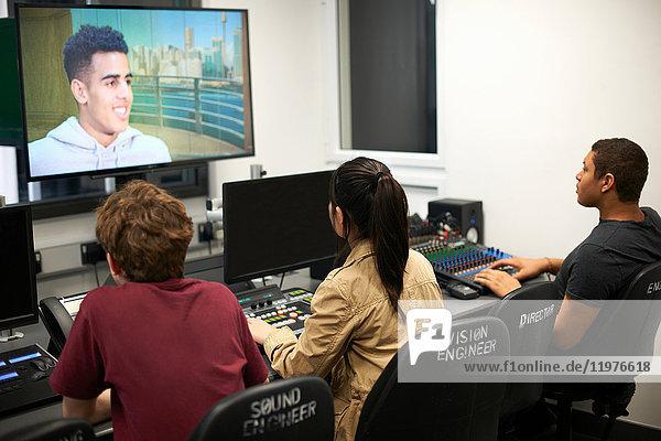 Junge männliche und weibliche College-Studenten am Mischpult beim Fernsehen