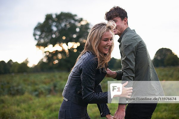 Young couple laughing and fooling around in field