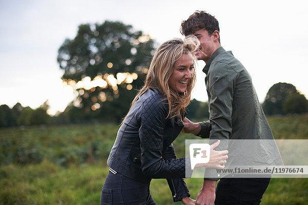 Junges Paar lacht und albert auf dem Feld herum