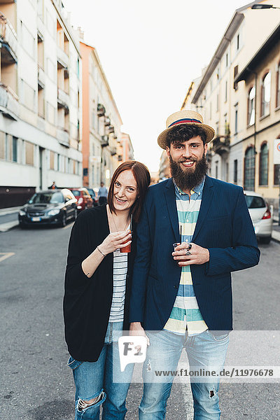 Portrait of happy couple with cocktails on city street