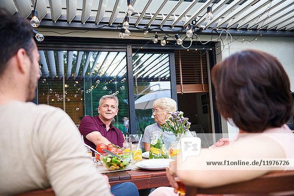 Über-Schulter-Ansicht einer älteren Frau und eines reifen Mannes beim Familienessen auf der Terrasse