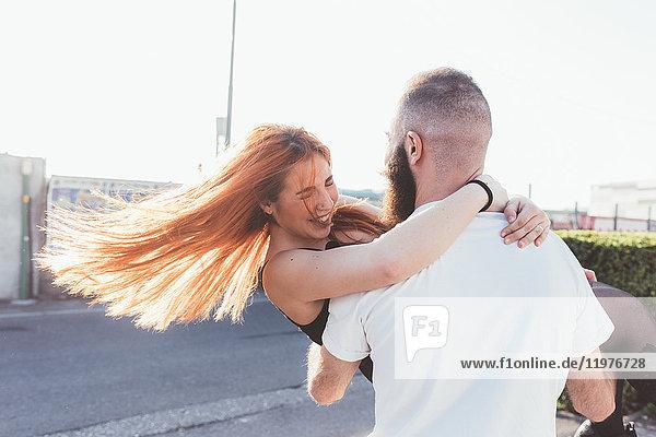 Mann trägt lächelnde Frau in den Armen