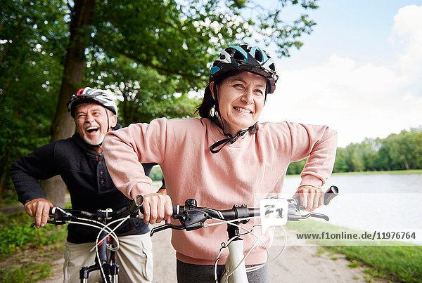 Mature couple cycling beside lake  laughing
