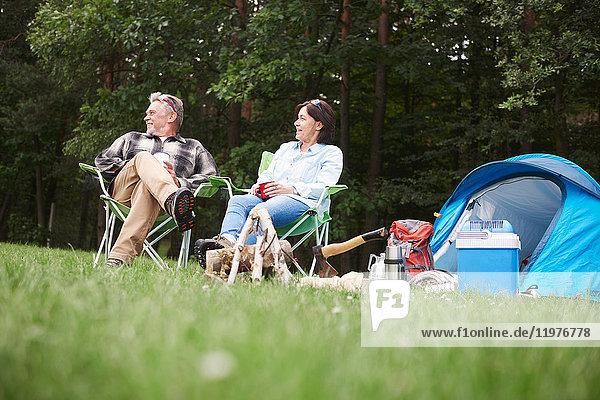 Älteres Paar sitzt in Campingsesseln neben dem Zelt  Blickwinkel niedrig