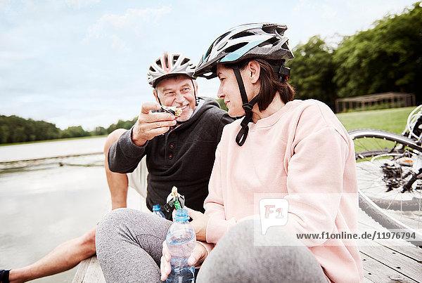 Ein erwachsenes Paar entspannt sich auf dem Steg  genießt einen Imbiss  Fahrräder hinter sich