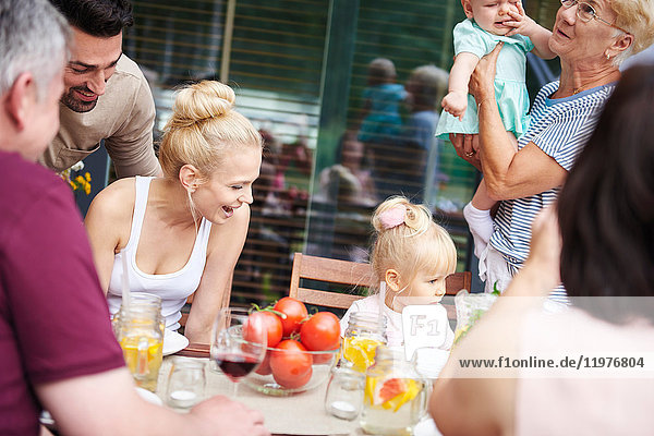 Three generation family with baby girl and female toddler at family lunch on patio table