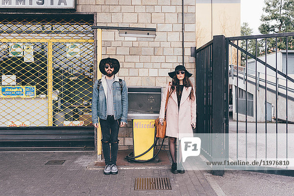 Portrait of young man and woman  in street  standing side by side