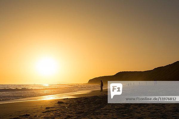Hinterleuchtete Touristen am goldenen Sonnenuntergangstrand  Newport Beach  Kalifornien  USA