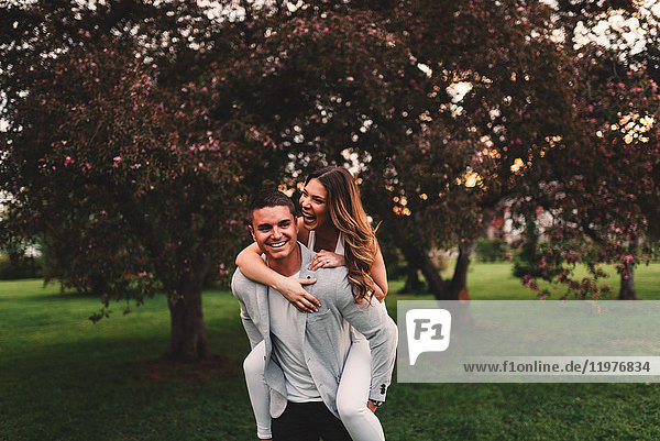 Young man giving girlfriend a piggyback in park at dusk