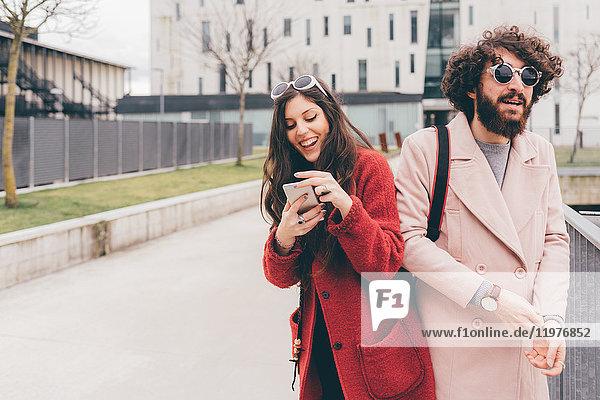 Junges Paar im Freien  junge Frau schaut auf Smartphone  lacht