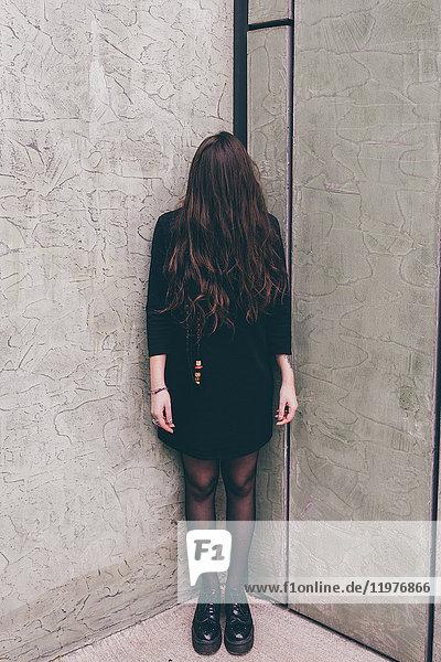 Porträt einer jungen Frau in der Ecke stehend,  die Haare bedecken das Gesicht