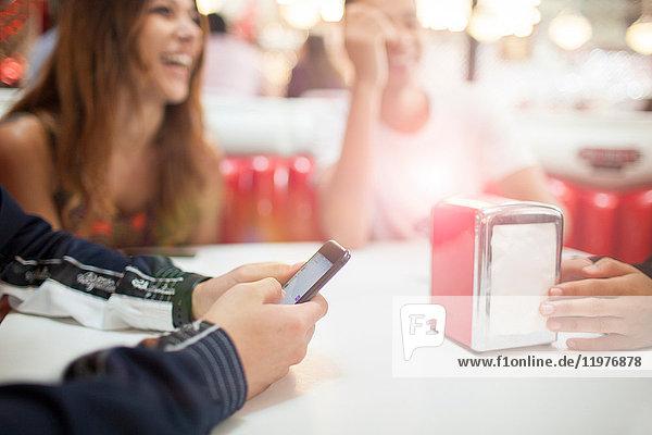 Gruppe junger Freunde sitzt im Diner  junger Mann benutzt Smartphone  Mittelteil