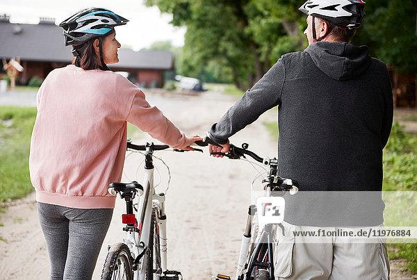 Älteres Paar zu Fuß mit Fahrrädern  Rückansicht