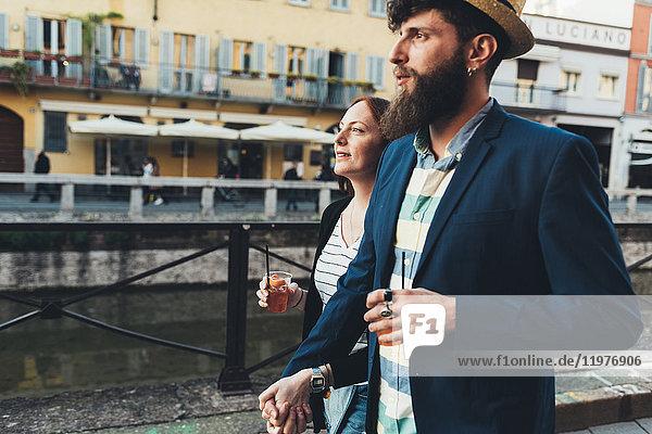 Paar mit Cocktails am Stadtkanal entlang schlendern Paar mit Cocktails am Stadtkanal entlang schlendern