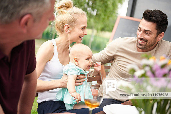 Couple with baby daughter at family lunch on patio
