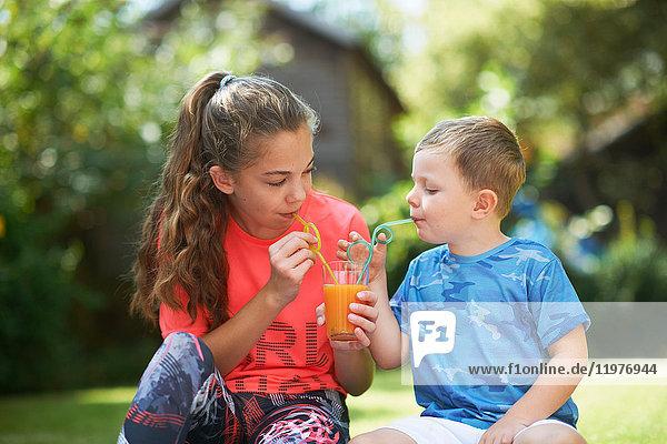 Teenager-Mädchen und Bruder teilen sich frischen Smoothie im Garten