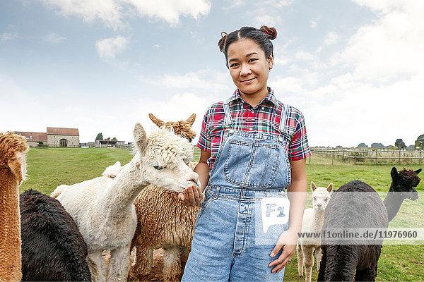 Porträt einer Frau mit Alpakas auf einem Bauernhof