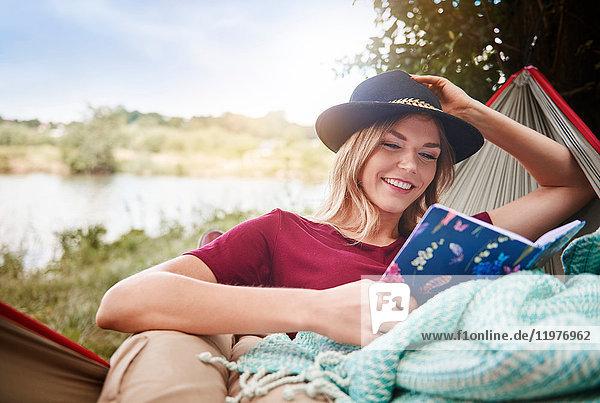 Frau entspannt sich in Hängematte und liest Buch  Krakau  Malopolskie  Polen  Europa