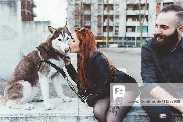Rothaarige Frau küsst Hund
