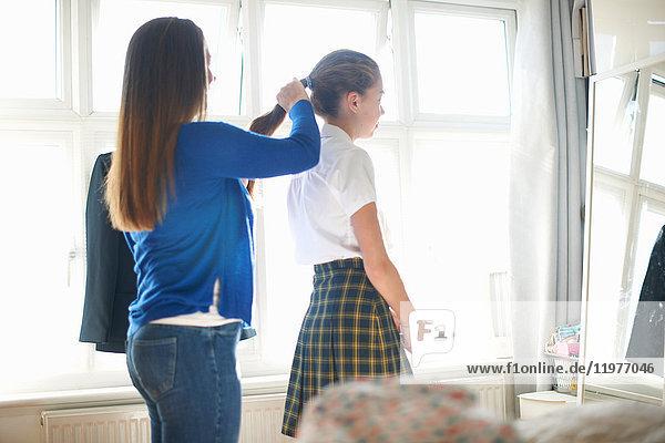 Mutter steckt der Tochter einer Teenager-Schülerin die Haare in den Pferdeschwanz