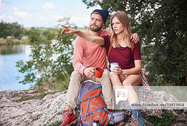 Couple hiking  sitting on rocks holding enamel mugs  Krakow  Malopolskie  Poland  Europe