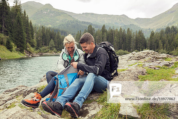 Couple hiking  sitting by lake looking at smartphone  Tirol  Steiermark  Austria  Europe