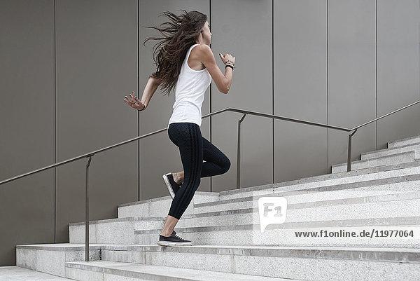 Junge Frau  die eine Treppe hinaufläuft  niedriger Blickwinkel