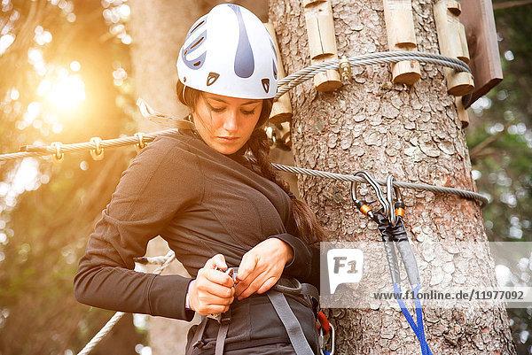 Teenager-Mädchen auf Baum  das sich auf Hochseilgarten vorbereitet