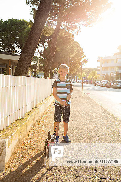 Portrait of boy with dog in street looking at camera smiling