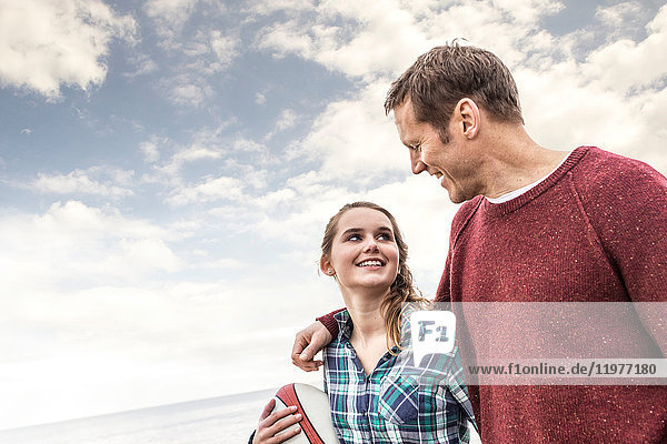 Vater und Tochter gehen gemeinsam am Strand spazieren