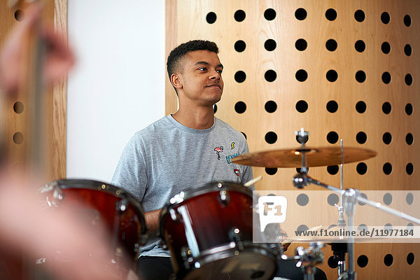 Young male college student playing drums in recording studio