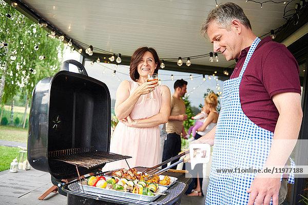 Erwachsenes Paar grillt beim Familienessen auf der Terrasse