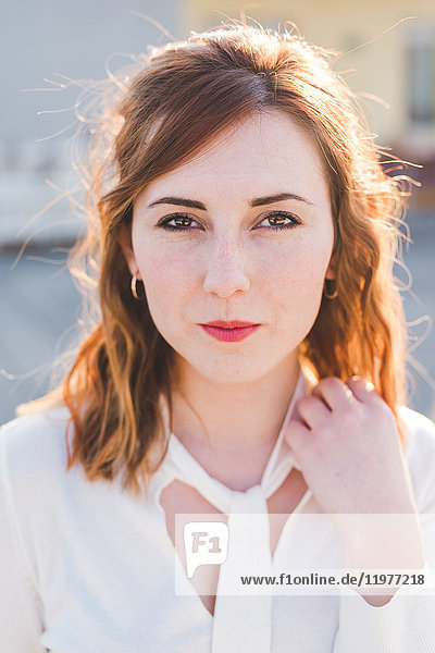 Portrait of beautiful young woman with hand in red hair
