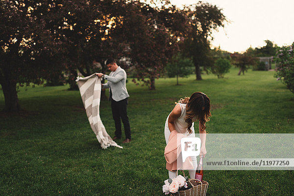 Junges Paar bereitet in der Abenddämmerung im Park eine Picknickdecke und rosa Champagner