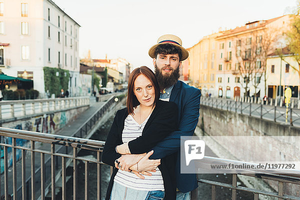 Portrait of cool couple by city canal
